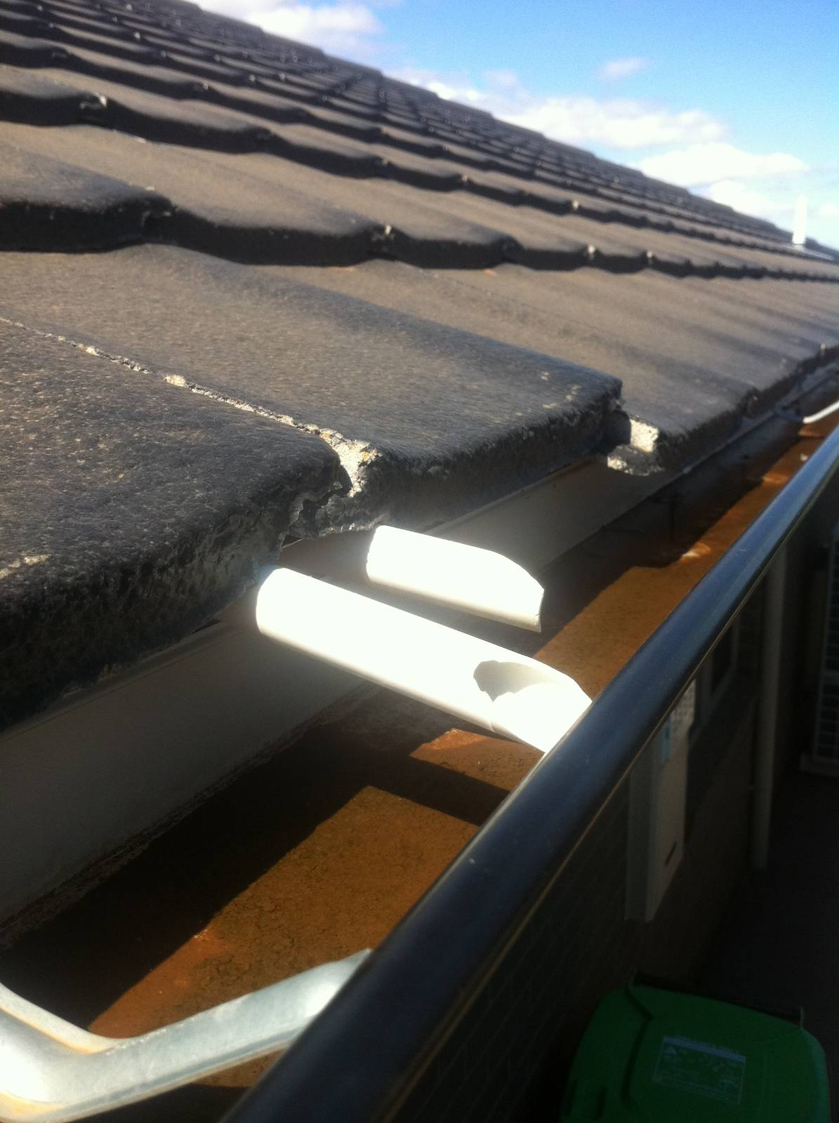Pipe sticking out underneath roof tile into guttering?